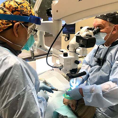 Dr. Kaban working with a microscope on a patient