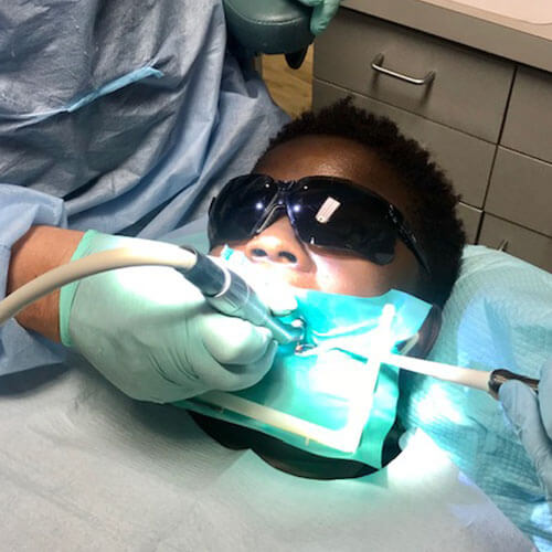 Patient wearing glasses while being treated by dentist