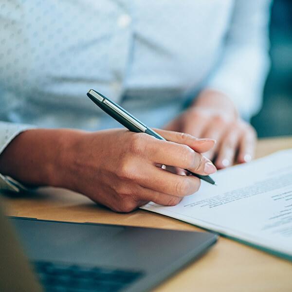 A woman writing files next to a laptop